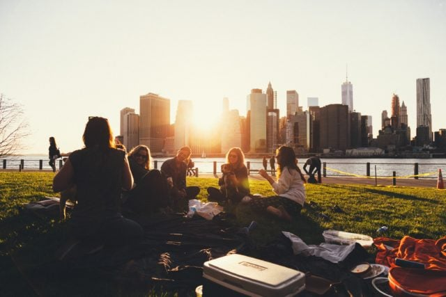 This image shows college students doing school work in a park.